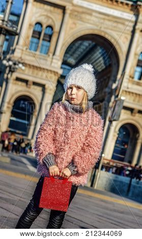 Rediscovering things everybody love in Milan. Full length portrait of modern girl with red shopping bag standing at Piazza del Duomo in Milan Italy