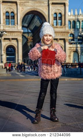 Rediscovering things everybody love in Milan. Full length portrait of surprised trendy girl with red shopping bag in Milan Italy