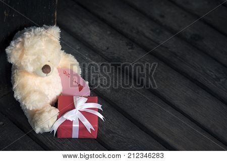 Teddy bear and label with message - Red gift box with white tied bow and a cute teddy bear toy holding a message on a rustic wooden floor