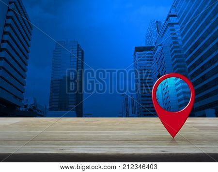 Map pin location button on wooden table over modern office city tower Map pointer navigation concept