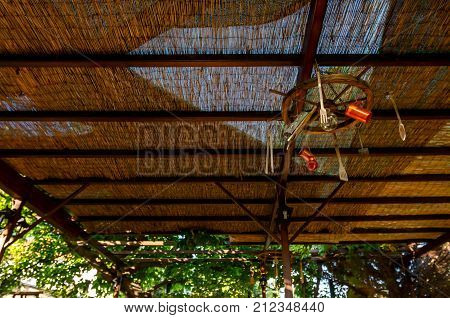 Abstract scene with wooden rudder and retro equipment for cooking hangs from the ceiling as decoration at traditional Greek tavern restaurant.