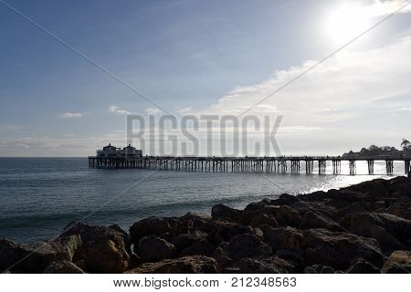 Malibu pier stretching out into the ocean in the late afternoon