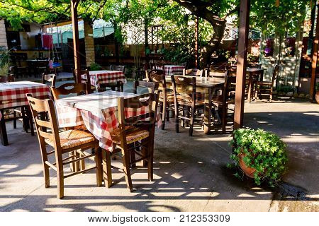 Chairs and tables in typical outdoor Greek tavern in morning sunlight with shadows.