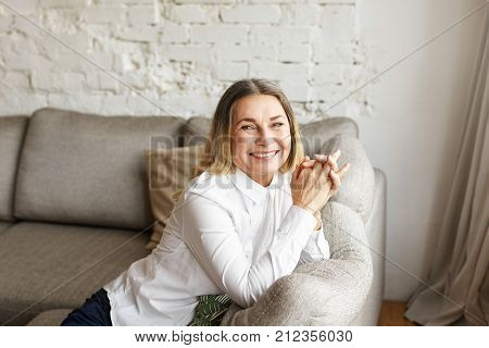 Joyful positive mature female dressed in white blouse relaxing in her living room. Beautiful elegant middle aged woman feeling happy and relaxed while having rest on comfortable sofa at home
