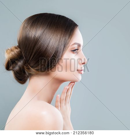Perfect Female Face Closeup. Spa Woman with Healthy Skin touching her Hand her Face Profile
