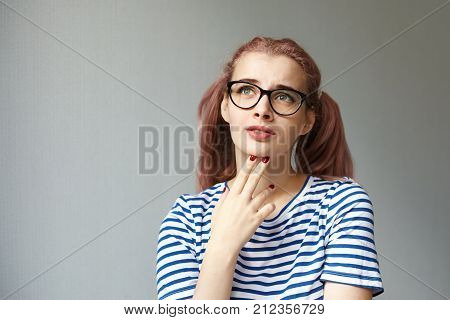 Thoughts ideas and contemplation concept. Headshot of thoughtful upset pink haired teenage girl facing problems at school looking up and raising eyebrows her grimace expressing frustration