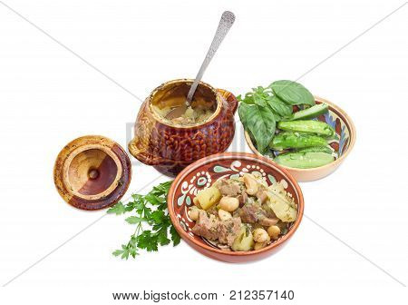 Ukrainian version of the dish Chanakhi - potatoes with meat mushrooms and haricot beans roasted in a clay pot in a clay bowl and lightly salted cucumbers on a white background closeup