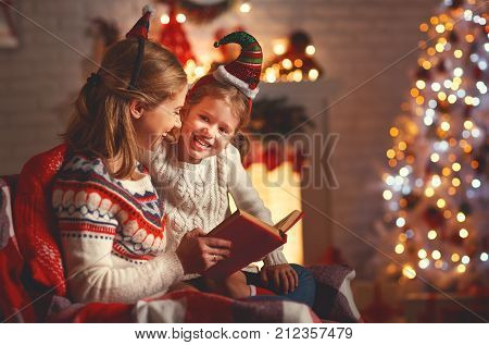 Christmas Eve. family mother and child daughter reading magic book at home near the fireplace and Christmas tree