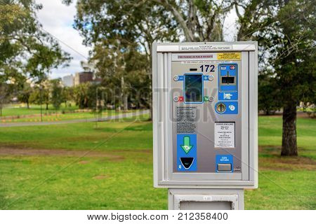 Adelaide Australia - August 27 2017: Parking meter installed near St. Peter's Cathedral in Adelaide CBD with cars parked along the street