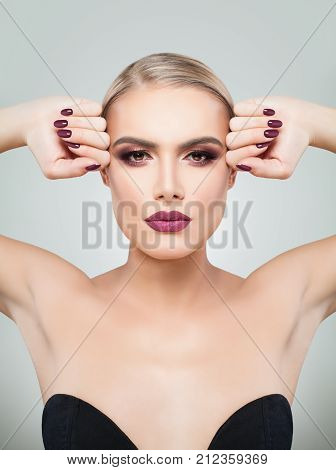 Beauty Sexy Woman with Perfect Professional Holiday Makeup. Violet Color of Eyeshadow Lips and Nails. Beauty Girl's Face on Grey Background
