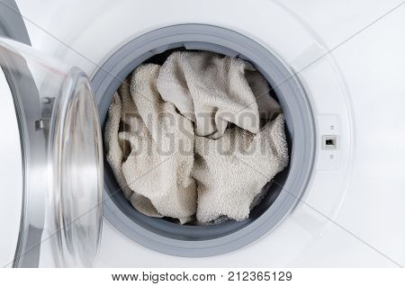 white clothes wash, open washing machine with towel, closeup