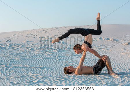 Couple of young sporty people practicing yoga lesson with partner, man and woman in yogi exercise, arm balance pose, working out, indoor full length. Yoga practice on the sand