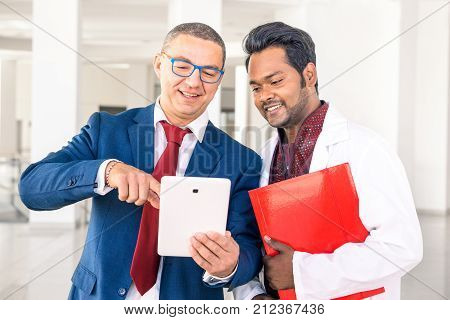 Young Indian doctor with businessman talking in hospital hallway - Salesman holding pad showing health care equipment at asian medical director - Concept of sales business deals with multiracial men