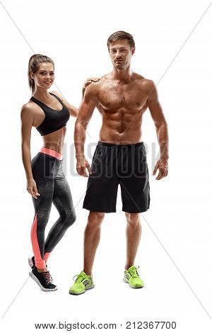 Sport, fitness, workout concept. Fit couple, strong muscular man and slim woman posing on a white background. A man in shorts and a naked torso and a woman in sportswear