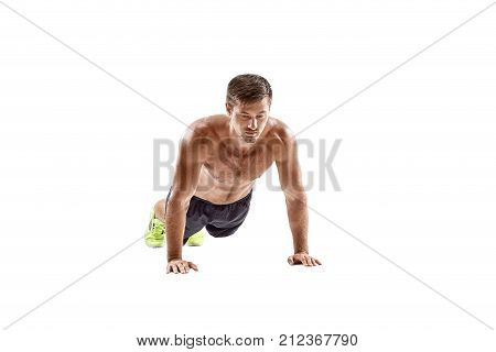 Push up fitness man doing push-up bodyweight exercise on gym floor. Athlete working out chest muscles strength training indoors. Horizontal. Copy space