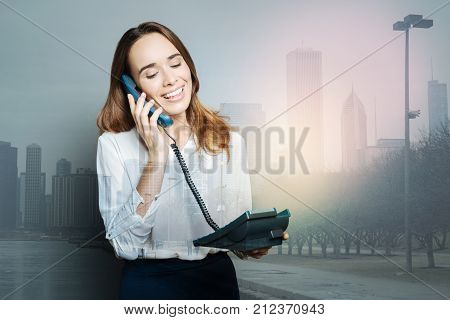 Phone call. Joyful delighted positive woman smiling and holding a phone receiver while making a phone call