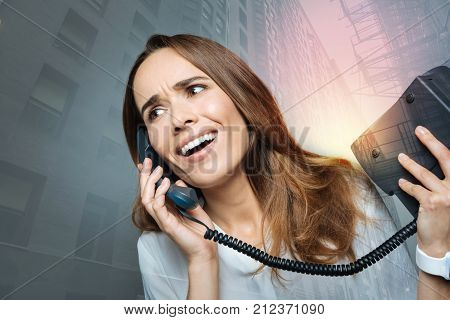 Distance communication. Positive emotional nice woman holding a phone receiver and talking on the phone while discussing work