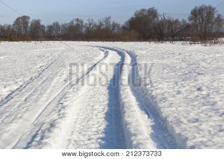 Footprints in the snow left by a snowmobile