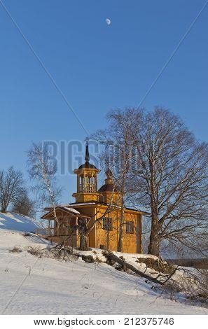 Wooden chapel on a sunny winter day on a background blue sky with the moon. Village Markovskaya Verkhovazhsky District Vologda Region, Russia
