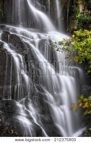 Eastatoe Falls is a beautiful 60 foot waterfall near Rosman North Carolina. Seen here in autumn. This is just a small portion of the falls showing the twist and turns of the water as it flows down.