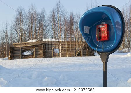 Verkhovazhye, Vologda region, Russia - 27 February 2015: Payphone on the background ruined wooden house in the backwoods Russian