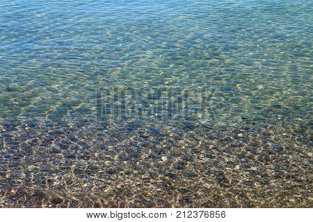 The picture was taken on the Black Sea. In the photo unusual light effects on the sea surface near the shore. Through the clear water can see the seabed.