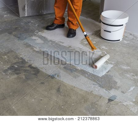 Worker puts primer with roller on concrete floor in room of unfinished apartment
