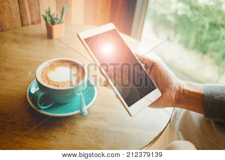 Hand Of Business Woman Hold Smart Phone Has Flare On Top Of Screen. Cup With Coffee  Placed On Wood