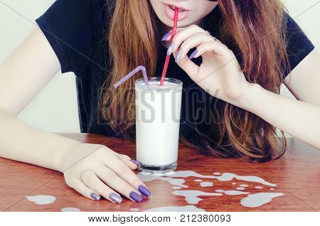 a girl drinks milk from a glass