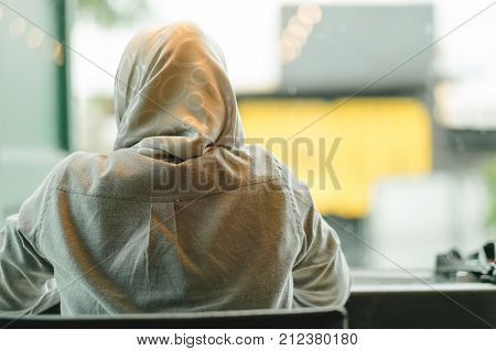 young muslim woman wearing gray shirt sit in a restaurant with window glass are background. this image for people person islamic religion culture place concept