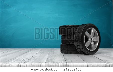 3d rendering of a single car tire leaning on three tires standing on a wooden surface in front of blue background. Spare wheels. Car service. Changing automobile parts.