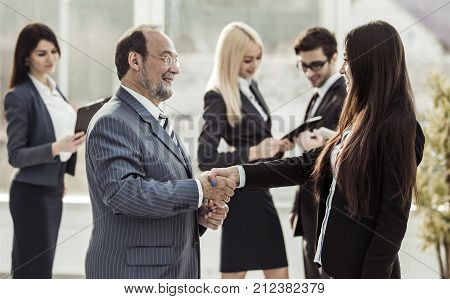 welcome handshake between lawyer and client on the background of business team in a modern office