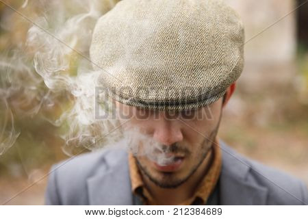 A man with a stubble and in a hat stands smoking a cigar and starting a thick cigar smoke. Retro. Outdoors.Close up.