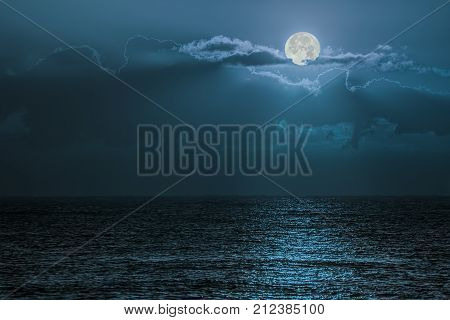 Blue moon light reflecting off ocean. Romantic twilight moonlight glistening off the surface of sea water. Lunar influence.