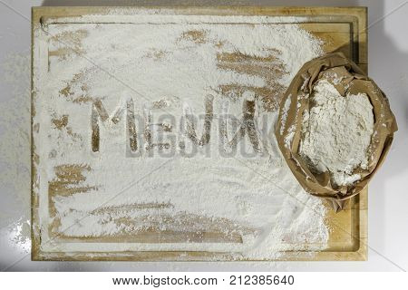 Rough wooden rectangular used cutting board background with paper sack of flour and menu word inscribed with finger directly from above on white background
