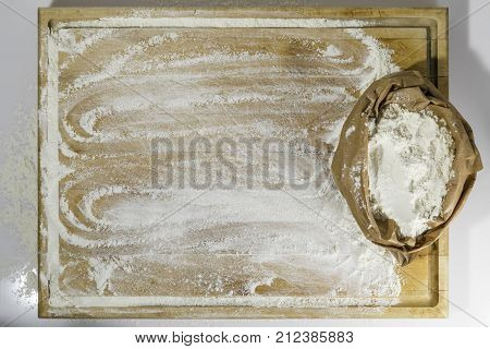 Rough wooden rectangular used cutting board on white background with paper sack of flour and flour strewed directly from above