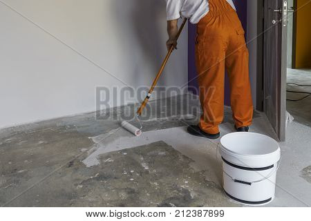 Interior of apartment under construction. Worker holding a roller and puts primer on concrete floor