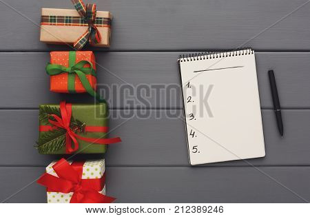 Presents for any holiday background. Frame of colorful gift boxes and open notebook for shopping list, copy space on gray wood, top view. Preparing for christmas, new year or valentine celebration.
