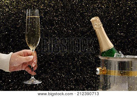 Celebrating new year, birthday, xmas party. Bottle of champagne in a bucket, female hand with flute on black backgroud with golden glitters, copy space. Mockup for postcard