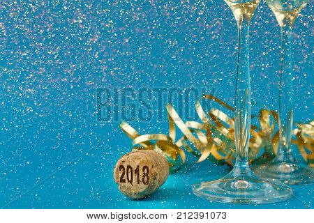 Champagne flutes and bottle cork with 2018 numbers at blue holiday background with golden glitters and tinsel. Celebrating christmas, new year or birthday. Mockup for xmas postcard, crop