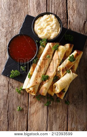Mexican Taquitos With Chicken And Cheese Stuffing Close-up, And Sauces. Vertical Top View