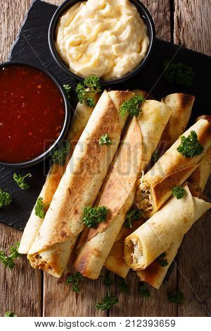 Taquitos With Chicken And Cheese Close-up, As Well As Sauces. Vertical Top View