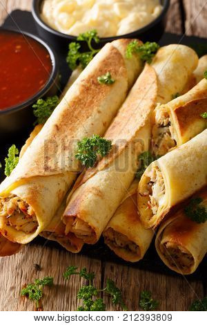 Mexican Taquitos With Chicken And Cheese Stuffing Close-up, And Sauces. Vertical