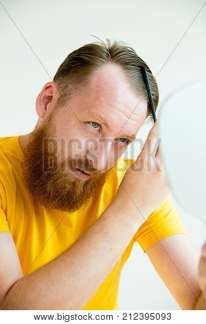 A portrait of a guy trimming his beard and doing his hair poster