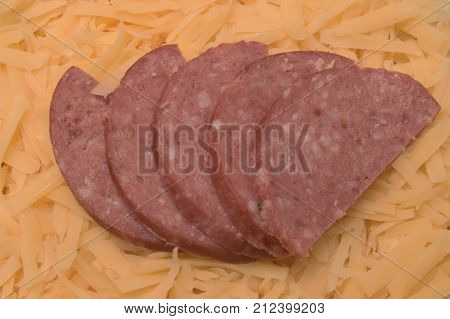 Five pieces of sliced salami on yellow cheese background