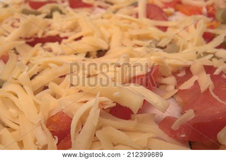 yellow grated cheese with red tomatoes, green olives and ham