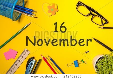 November 16th. Day 16 of last autumn month, calendar on yellow background with office supplies. Business theme.