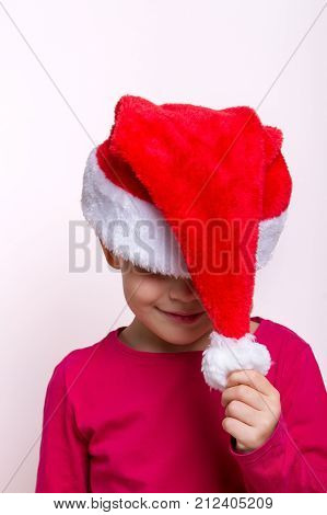 child in a santa hat portrait hides his face, pulls for a pompom, modest