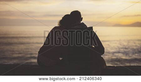 Couple hugging on background beach ocean sunrise silhouette two romantic people cuddling and looking on rear view evening seascape hipster with dog enjoy sunset together travel holidays vacation love relax concept