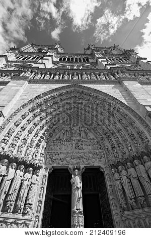 Notre-Dame de Paris cathedral's façade or west front, an imposing gothic monument with various bust looking down at the ones entering it.